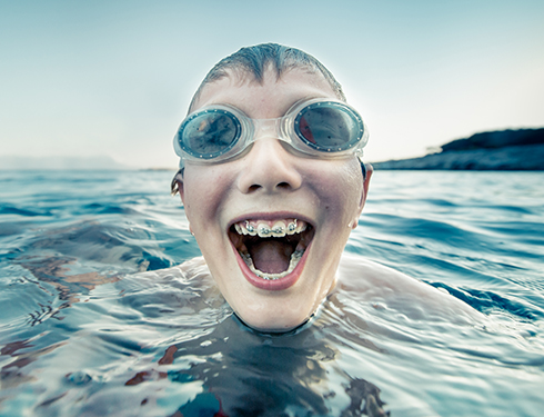 Boy swimming with braces